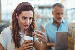 Pretty brunette using her smartphone with coffee in her hand Stock Photos