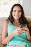 Pretty brunette using her smartphone on the couch Royalty Free Stock Images