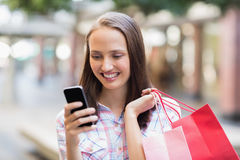 Pretty brunette using her smartphone and holding shopping bag Stock Image