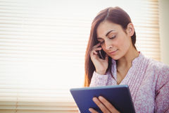 Pretty brunette using her tablet Royalty Free Stock Photos