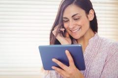 Pretty brunette using her tablet Stock Photo