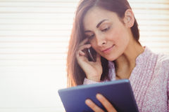 Pretty brunette using her tablet Stock Photography