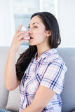 Pretty brunette using inhaler on couch Stock Photos