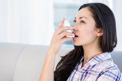 Pretty brunette using inhaler on couch. At home in the living-room stock image