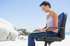 Pretty brunette using laptop on the beach sitting on swivel chair Royalty Free Stock Image