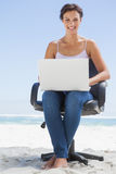 Pretty brunette using laptop on the beach sitting on swivel chair Stock Photo