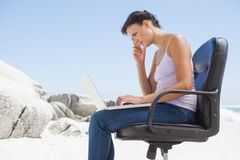 Pretty brunette using laptop on the beach sitting on swivel chair Stock Photos