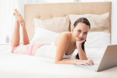 Pretty brunette using laptop on bed Stock Image
