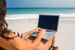 Pretty brunette using laptop on deck chair Stock Image