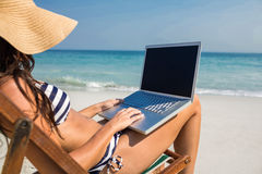 Pretty brunette using laptop on deck chair Royalty Free Stock Photos