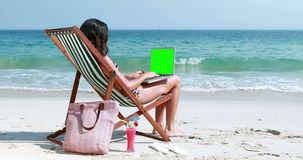 Pretty brunette using laptop on deck chair. At the beach stock video footage