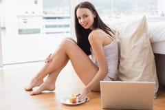 Pretty brunette using laptop sitting on floor Stock Photos