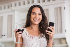 Pretty brunette using smartphone and having glass of wine Stock Photos