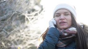 Pretty Brunette Using Smartphone Outdoor in Frosty Winter Weather. Smiling Girl Talking with Somebody by Mobile Phone. Standing in the Park in Sunny Morning stock video footage
