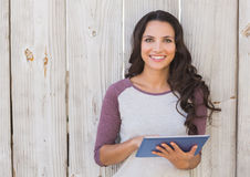 Pretty brunette using a tablet pc Royalty Free Stock Image