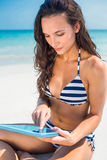 Pretty brunette using tablet pc at the beach Royalty Free Stock Photo