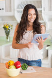 Pretty brunette using tablet pc and preparing salad Royalty Free Stock Photography