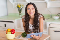 Pretty brunette using tablet pc and preparing salad Stock Images