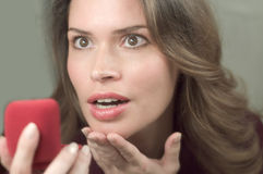 Pretty brunette is very happy to receive a present. In a red box Stock Photos