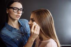 Pretty brunette visagiste using a makeup sponge Stock Photography
