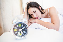 Pretty brunette watching alarm clock on bed Royalty Free Stock Images