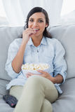 Pretty brunette watching tv with pop corn Royalty Free Stock Photos