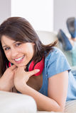 Pretty brunette wearing earphones around neck on the couch Royalty Free Stock Photo