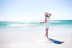Pretty brunette wearing straw hat and walking in the water Stock Photo