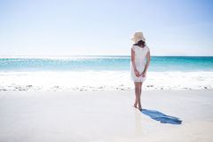 Pretty brunette wearing straw hat and walking in the water Royalty Free Stock Photography