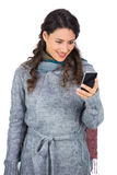 Pretty brunette wearing winter clothes holding her smartphone Stock Photos
