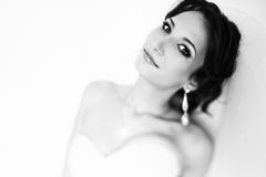 Pretty brunette in white dress looks confident and seductive Royalty Free Stock Photography
