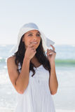 Pretty brunette in white sunhat looking away and touching hat Stock Photography
