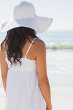 Pretty brunette in white sunhat looking at the sea Royalty Free Stock Photography