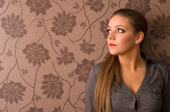 Pretty brunette woman. Portrait of pretty brunette woman with floral wallpaper in background Stock Photos