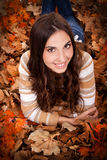 Pretty brunette woman in autumn leaves Stock Photos