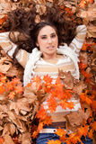 Pretty brunette woman in autumn leaves Stock Images