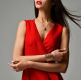 Pretty brunette woman in formal red dress on grey. Background Royalty Free Stock Images