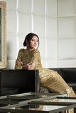 Pretty brunette woman in gold dress posing on sofa Stock Images