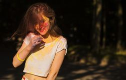 Pretty young model with hair in wind posing covered with colorfu. Pretty brunette woman with hair in wind posing covered with colorful powder Holi in the park Stock Photography