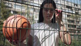 Pretty brunette woman holding basketball ball looking at the camera standing behind the mesh fence at the basketball. Portrait of brunette woman with basketball stock video