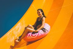 Brunette woman having fun on the water slide in aqua park. Pretty brunette woman on the inflatable ring having fun on the orange water slide in the aqua park royalty free stock image
