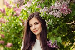 Pretty brunette woman with long healthy hair and natural makeup. On floral background outdoors royalty free stock photography