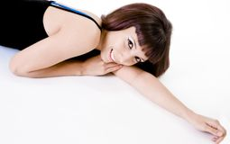 Pretty Brunette Woman Lying Down. Brunette woman lying down against a white surface--space for copy Stock Photos