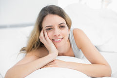 Pretty brunette woman lying on her bed smiling at camera Stock Photography
