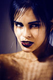 Pretty brunette woman with make up like demon at halloween, closeup scary background Stock Image
