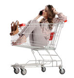 Pretty brunette woman phone speaking in empty shopping trolley. Isolated on white background Stock Photos
