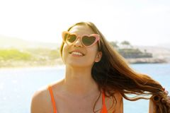 Pretty brunette woman in pink heart sunglasses on the beach. Holidays, vacation travel and freedom concept. Beautiful happy girl. In heart shaped sunglasses on stock photo