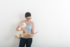 Pretty brunette woman reading book with her plush toy cat. Pretty brunette woman reading book with her plush toy cat Royalty Free Stock Photography