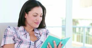 Pretty brunette woman reading a book stock video