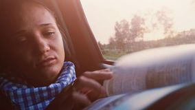 Pretty brunette woman reading a book while traveling in a car during beautiful sunset. 3840x2160. Beautiful brunette woman reading a book while traveling in a stock footage